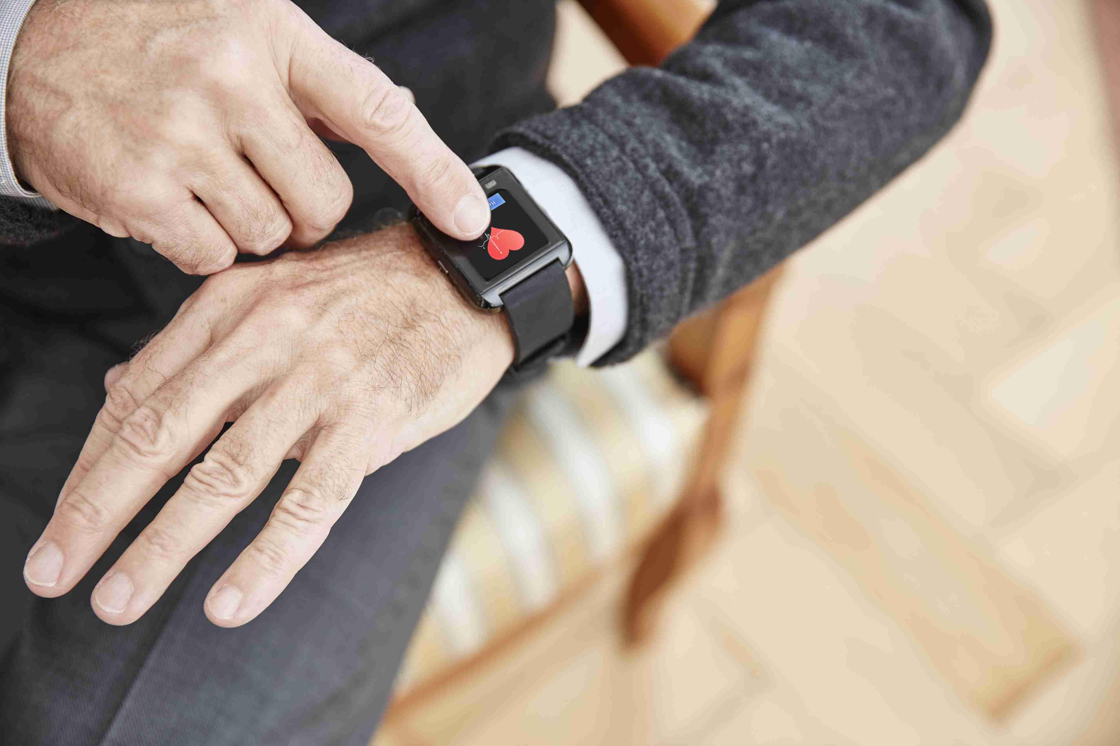 Senior man checking medical data on smartwatch