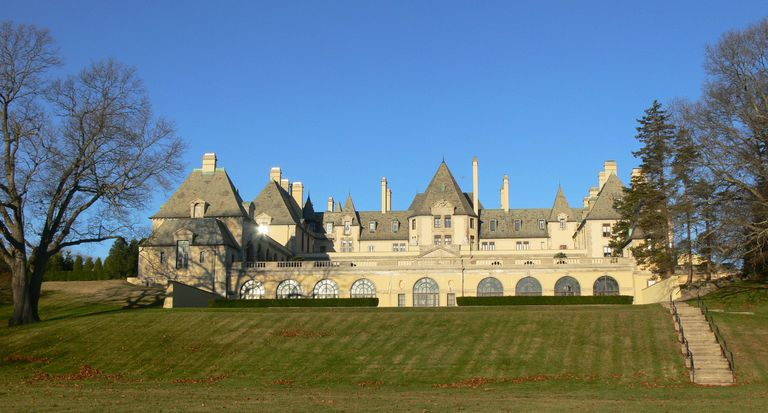 large horizontal-oriented estate with chateaux-like hipped roofs and tall chimneys
