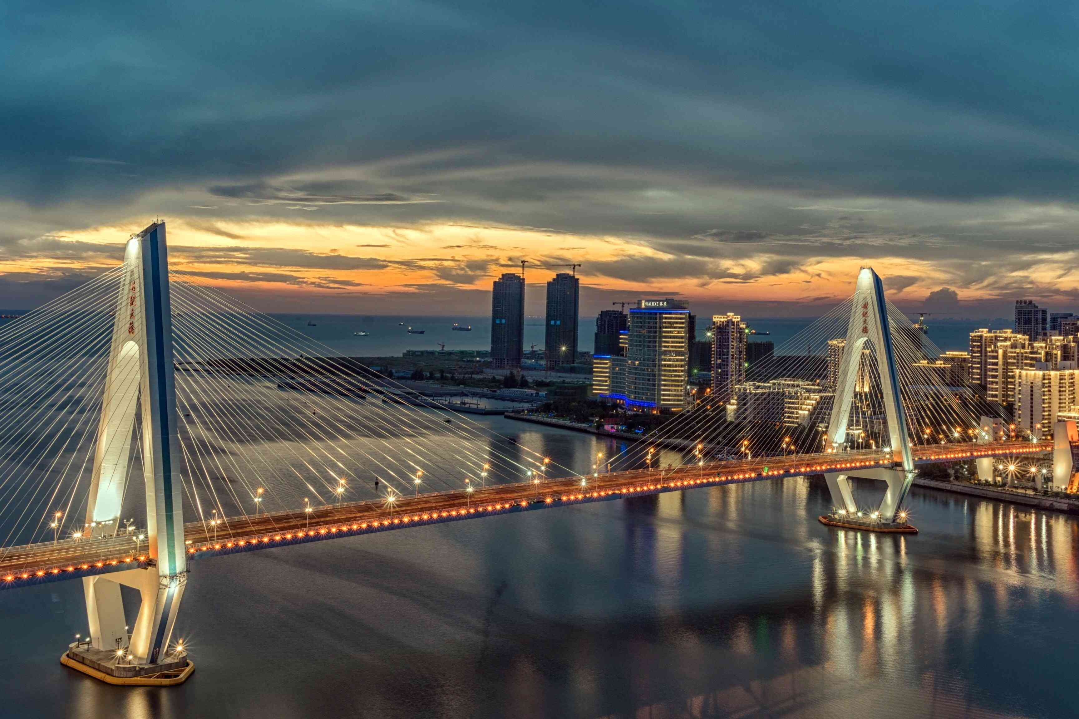 Modern cable-stayed bridge over river in city during sunset in Haikou