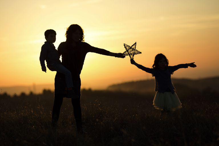 Silhouette of woman with two children, holding up a star