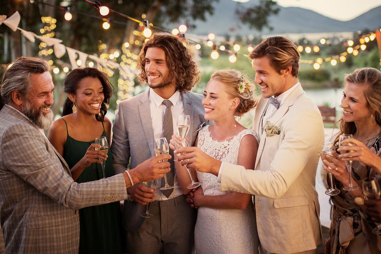 Young couple and their guests with champagne flutes during wedding reception in garden.