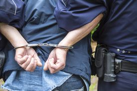 A man in handcuffs is led by an officer.