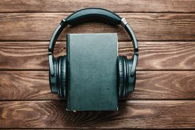 Headphones around a paper book.
