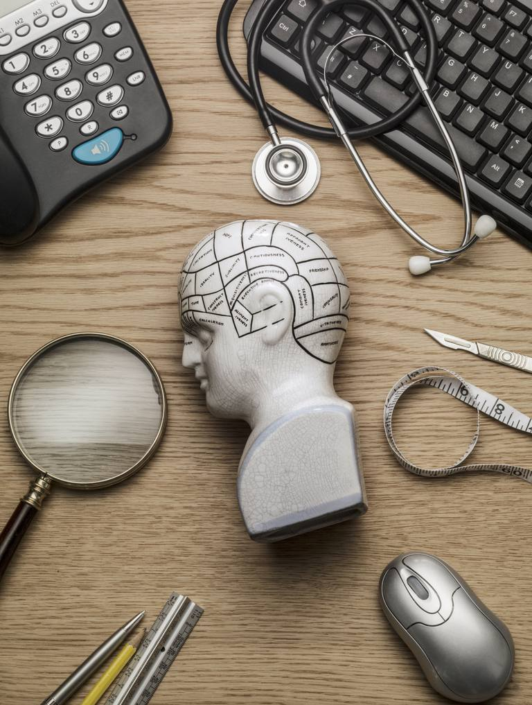 Instrumentos médicos, lupa, lápices, teléfono y teclado