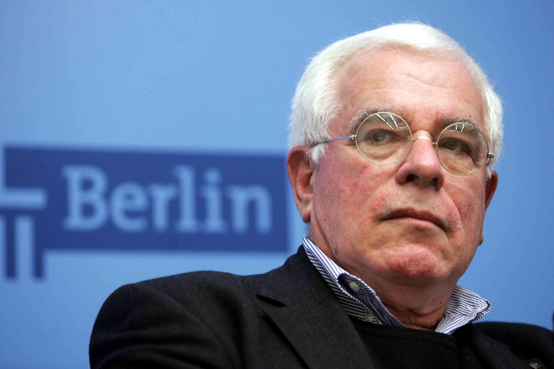 homme blanc, cheveux blancs, fines lunettes cerclées, signe Berlin en arrière-plan