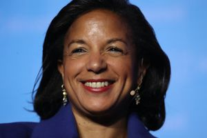 Susan Rice smiling at the camera in front of a blue background.