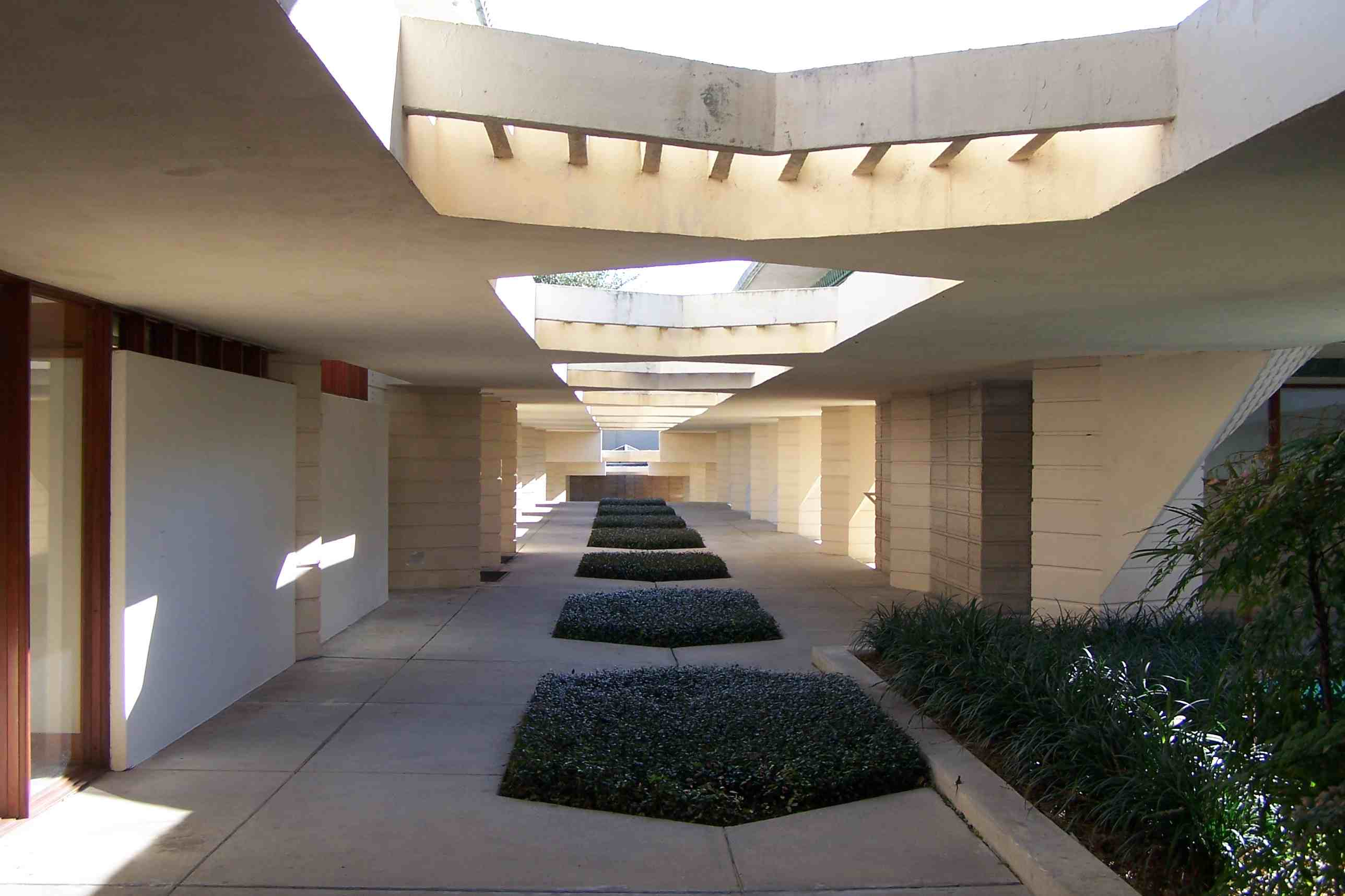 white concrete esplanade, partially covered walkway with vegetation
