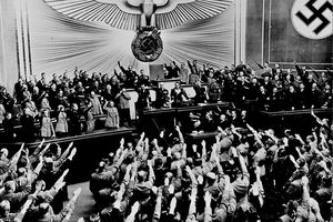 Hitler receives an ovation after announcing the Anschluss, black and white photograph with people saluting.