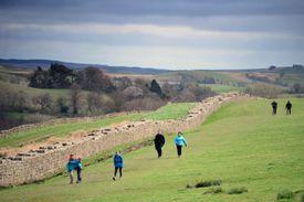 Hikers walk along Hadrian's Wall