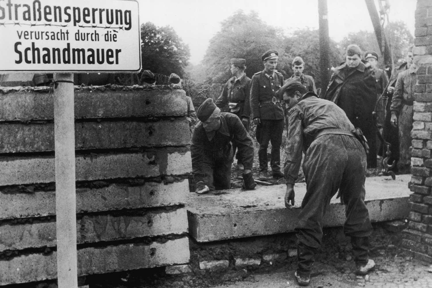Building the Berlin Wall in Germany, black and white photograph.