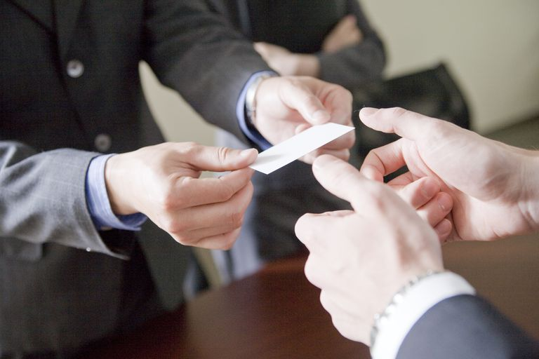 Close-Up of Businesspeople Passing Businesscard
