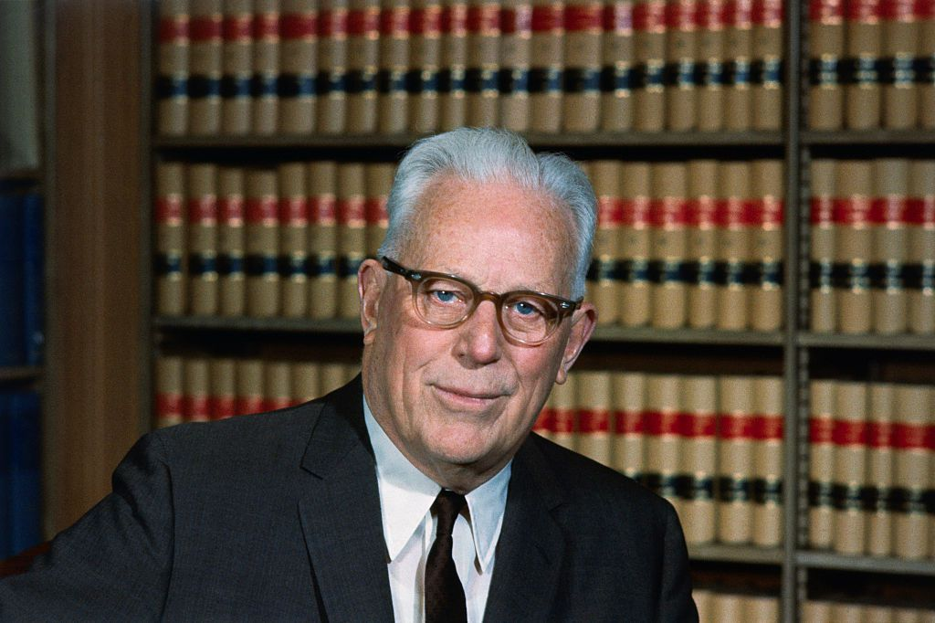 Color photograph of former US Supreme Court Chief Justice Earl Warren seated in his legal library.
