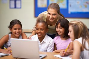 A teacher and her students learn from a laptop screen