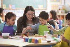 Teacher helping students in art class