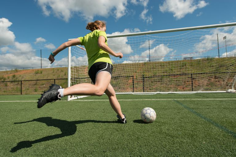 Female soccer player practicing shots.