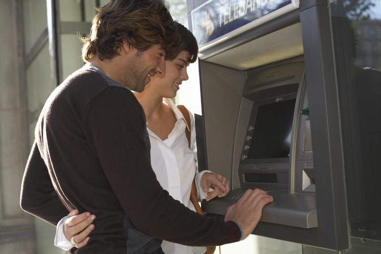 Young couple using cash machine