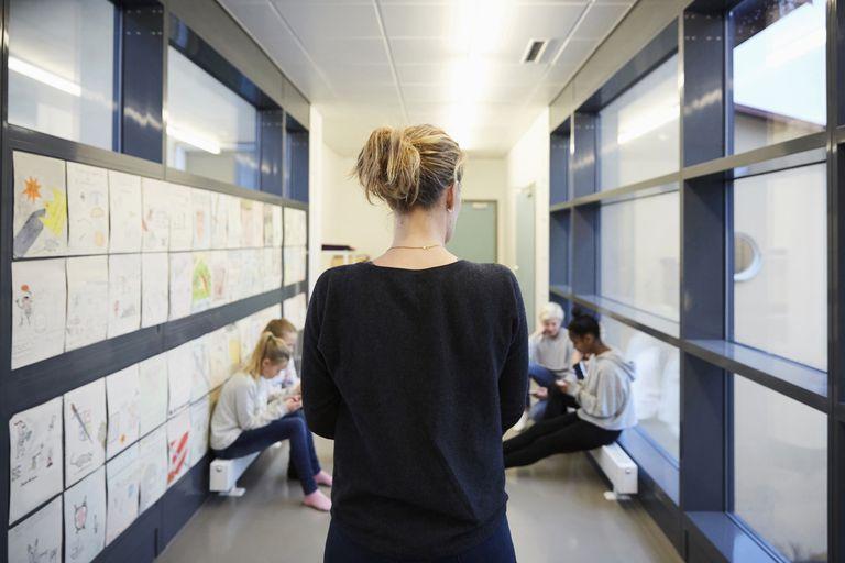 Rear view of teacher looking at students in school corridor