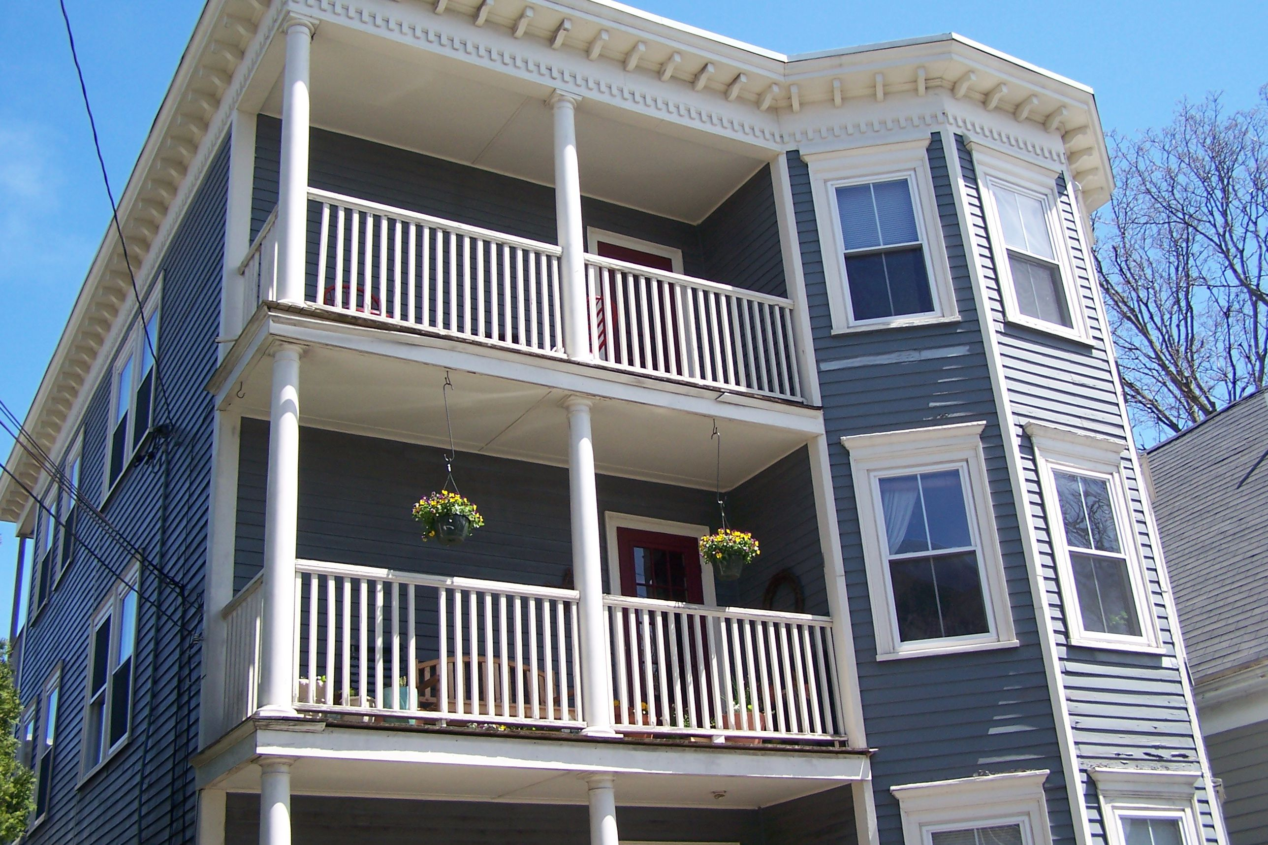 three-story wood apartment house with front porches and bay windows at each floor
