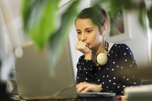 Girl with headphones on neck looking at laptop.