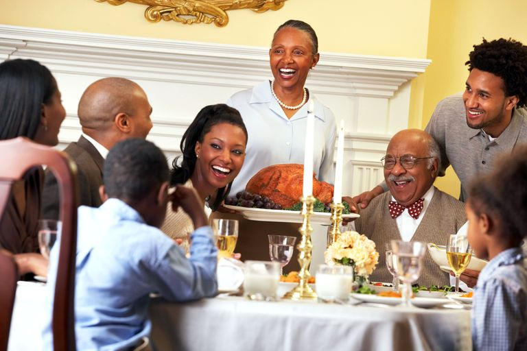 A large family is all smiles at Thanksgiving dinner