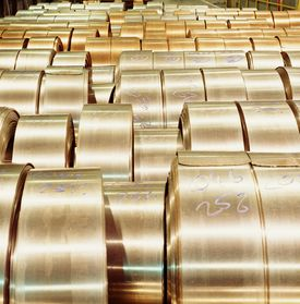 Rolls of brass sheet metal sitting in a warehouse setting ready for deliver to the customer.