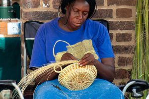 A gullah woman makes a sweetgrass basket in Charleston's City Market