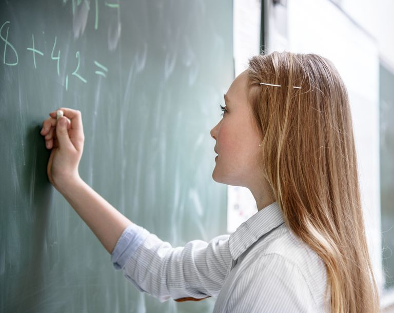girl doing math at blackboard
