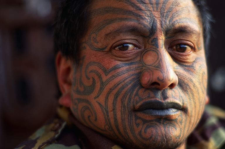Indigenous man with tattooed face close up.