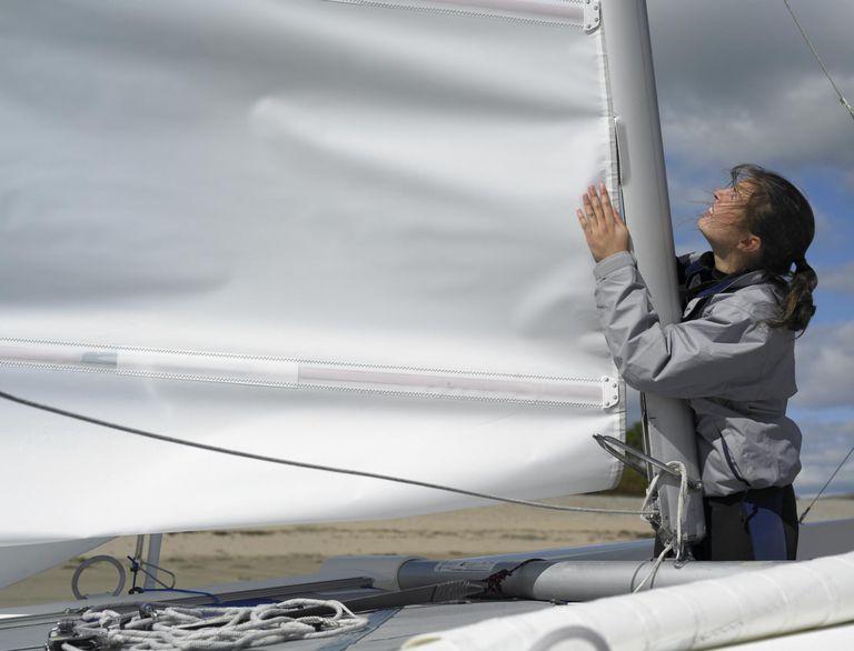 Woman holding sail of catamaran on beach