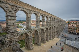 Two-story, stone aqueduct running through a Spanish city