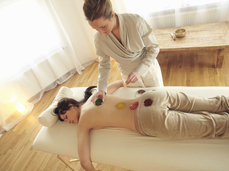 Female therapist placing chakra stones on womans back, overhead view