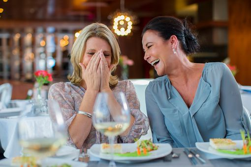 Two women at a restaurant laughing