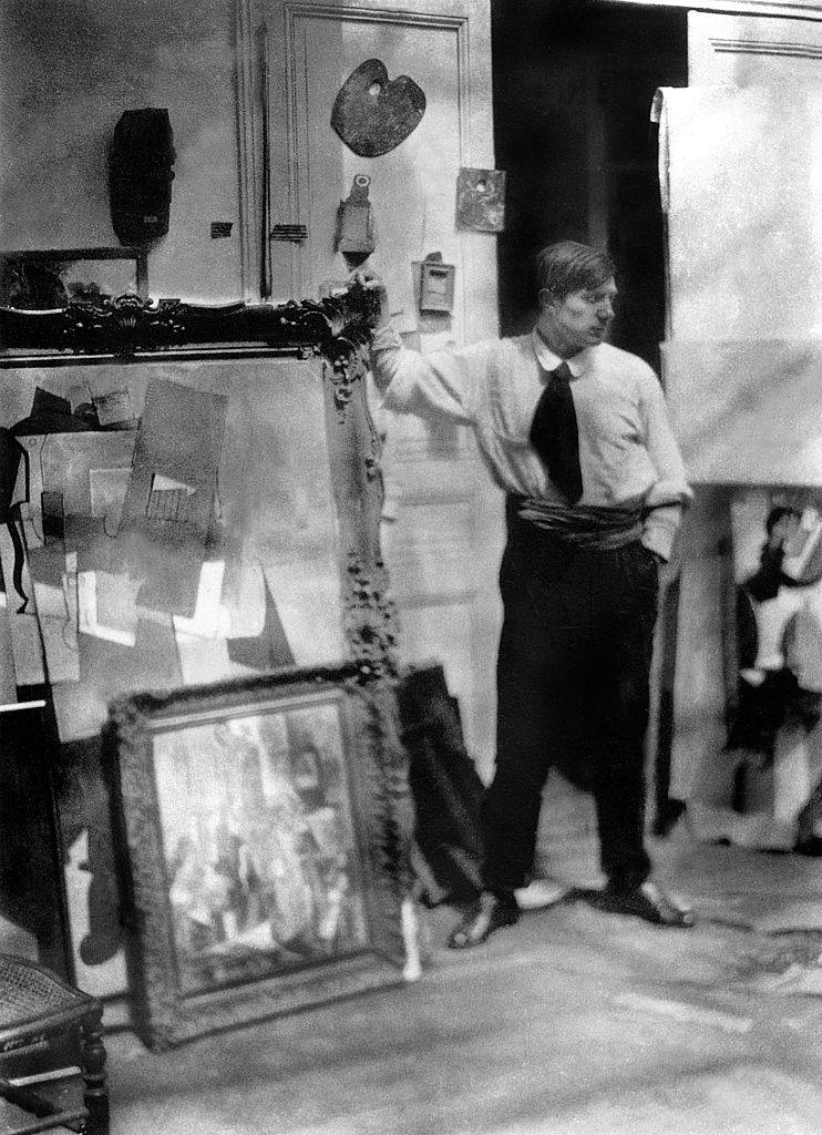 Picasso standing near framed paintings