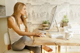 A woman performs internet research at the dining room table