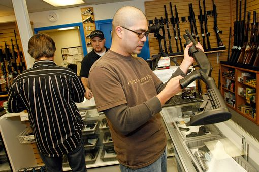Man holding a rifle at a gun store