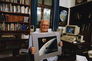 Image of Arthur C. Clarke in his home, with a bookcase in the back, sitting in front of his computer, holding up an artistic image of a spaceship flying in a planet's orbit.
