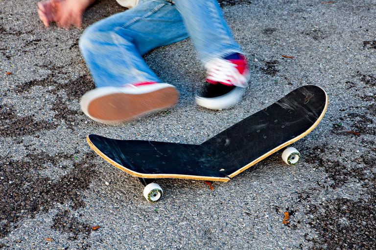 Man lying next to broken skateboard