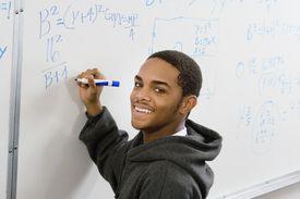 teen doing algebra on a white board