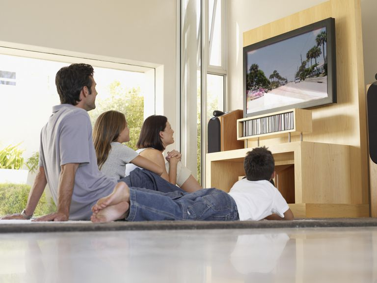 Family of four on floor watching television, ground view