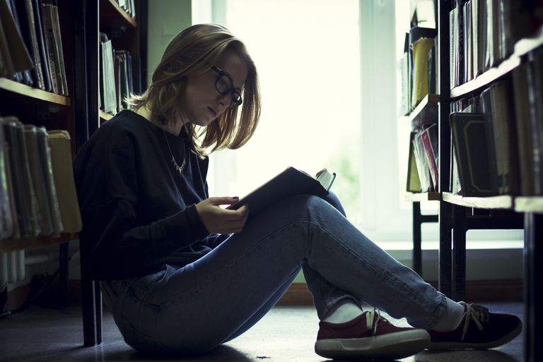 Caucasian woman reading book in library