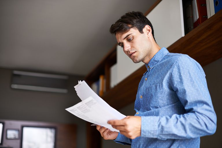 Man looking at stack of papers