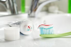 Toothbrush and toothpaste in the bathroom close up