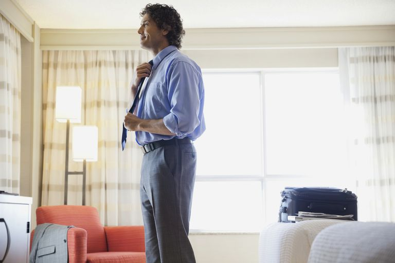 Businessman straightening tie in hotel room