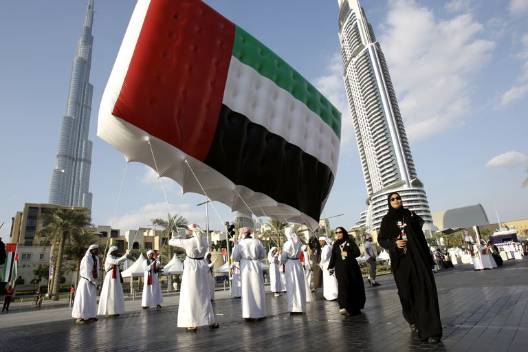 Emirati men and women carry UAE flag in front of Burj Khalifa during UAE National Day, Dubai
