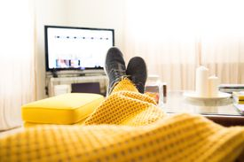 Man in sneakers wrapped in blanket on the couch