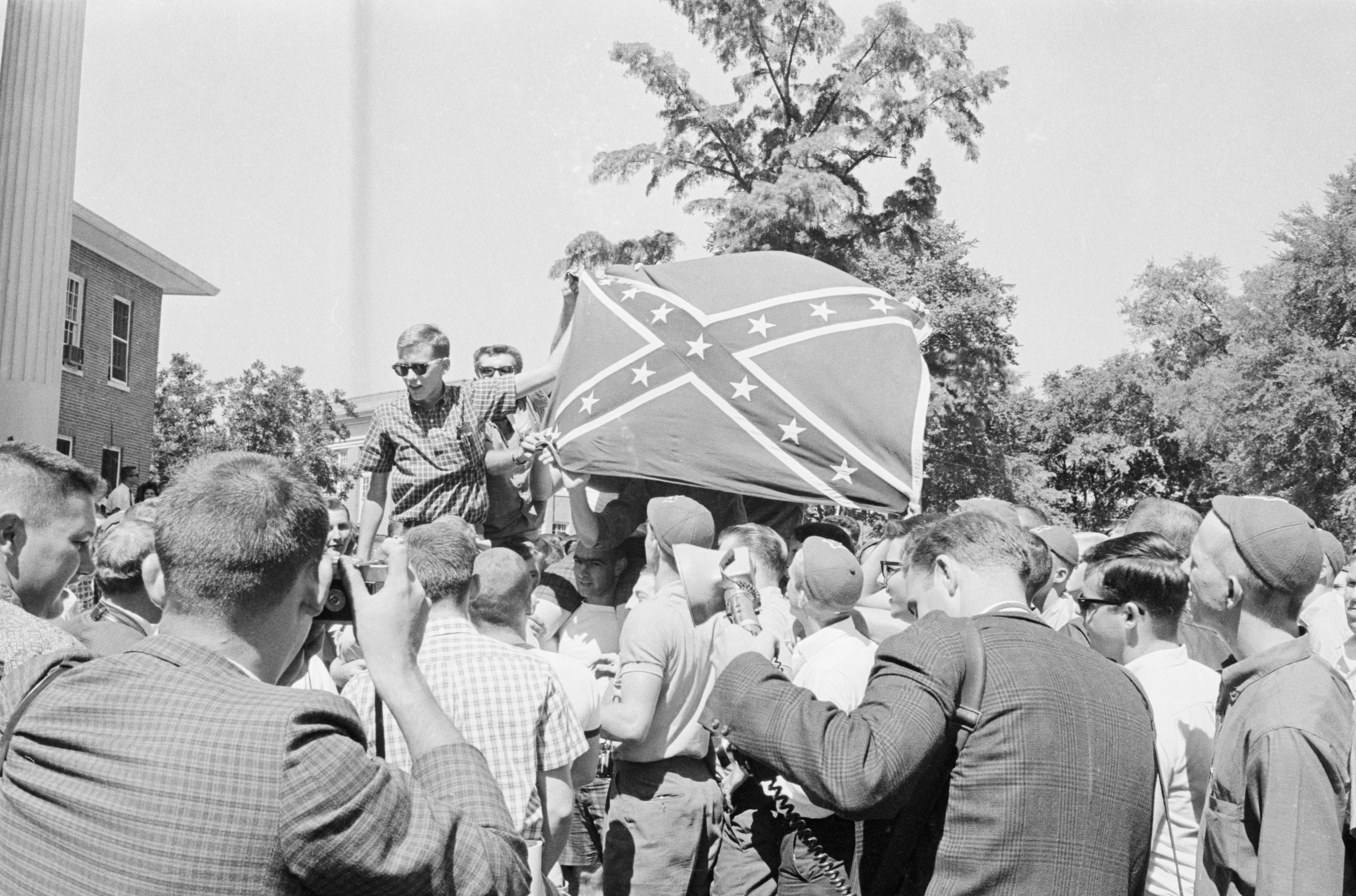 Students hoist a Confederate flag into the air during Ole Miss riot.