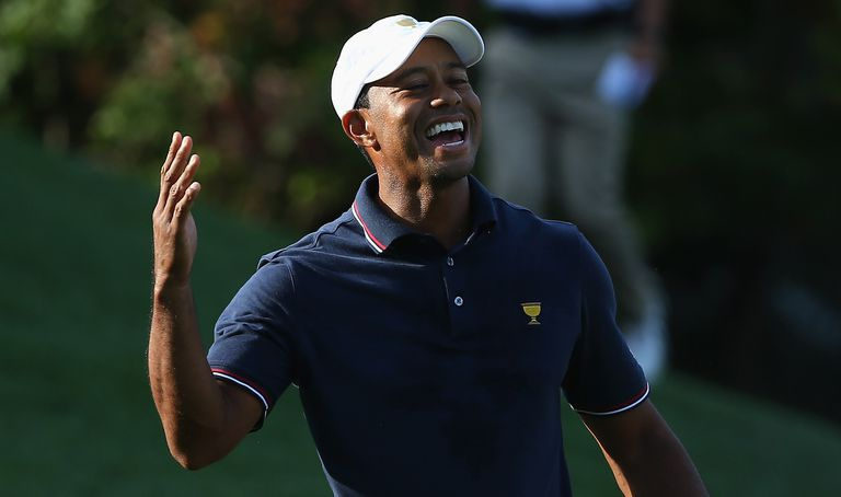 Tiger Woods of the U.S. Team celebrates after winning the 12th hole during the Day One Four-Ball Matches at the Muirfield Village Golf Club on October 3, 2013 in Dublin, Ohio
