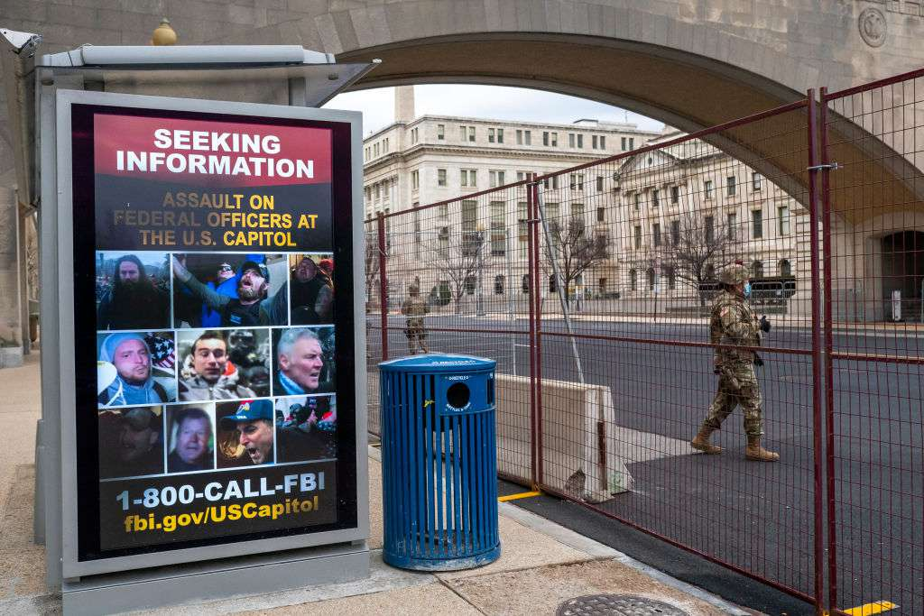 A National Guardsman walks past a poster seeking information on the U.S. Capitol attack on January 19, 2021.