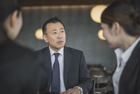 Japanese businessman talking to colleagues in business meeting, candid portrait