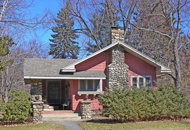 A large stone chimney is the dominant feature on this rose-colored bungalow